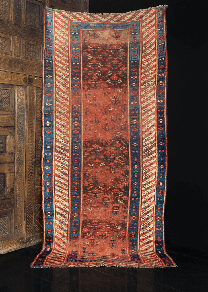 Kurdish rug handwoven during the first quarter of the 20th century in Northwest Iran. Small all over geometric pattern in blues and white atop a red ground. Beautiful abrash with a large candy stripe border.