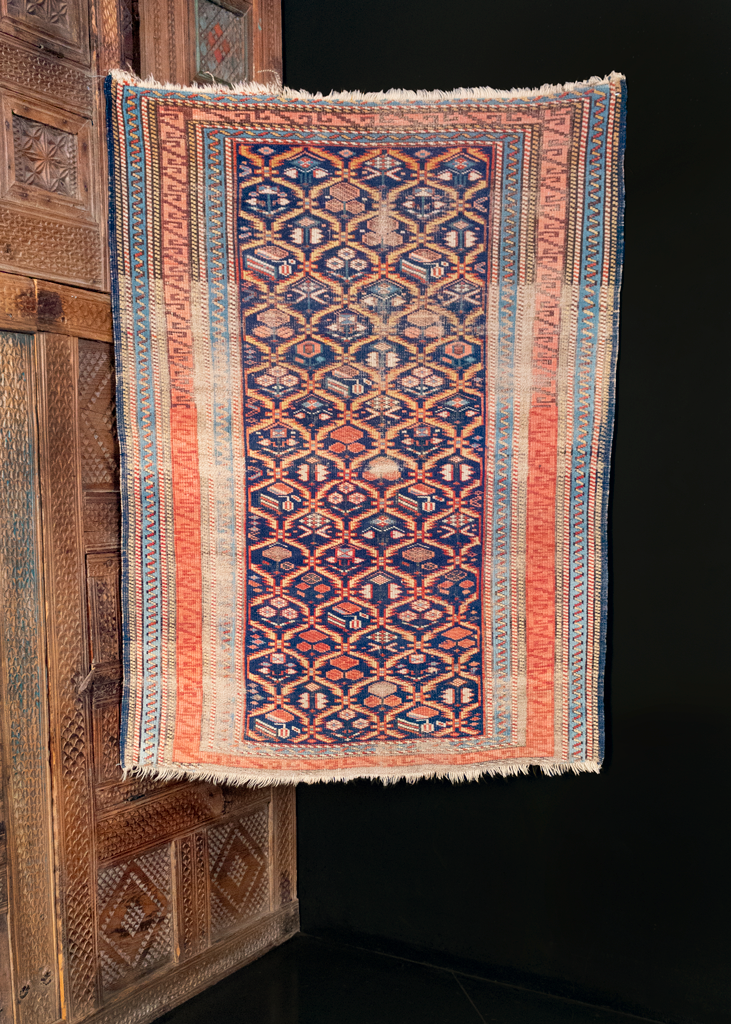 Kuba rug handwoven during the late 19th century in the Caucasus. Geometric flowers in a lattice design on an indigo blue field.