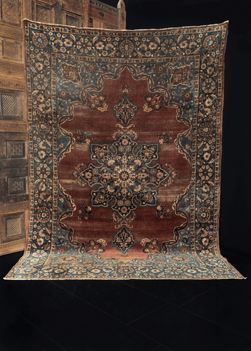 Antique Yazd rug handwoven in Central Iran during first quarter of 20th century. Floral central medallion on a deep maroon field. Ivory details lighten the floral design.