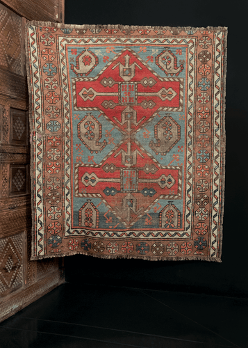 Kazak rug handwoven at the turn of the 20th century in the Caucasus. Features two bold geometric diamonds on top of a light blue ground.