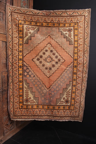Khotan rug handwoven second quarter of 20th century in Northwest China. Orange-pink peach tones and soft grey browns. Slightly off center medallion framed by small flowers