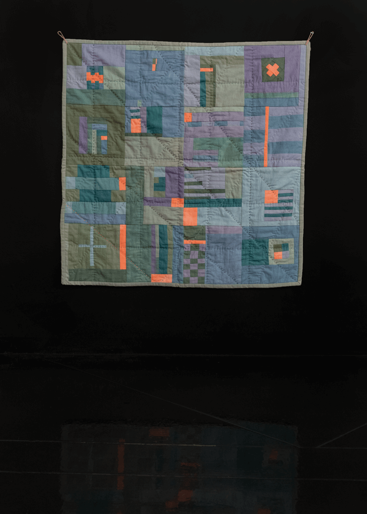 Handmade quilt with pops of bright orange atop a field of pastel greens, blues and purples.