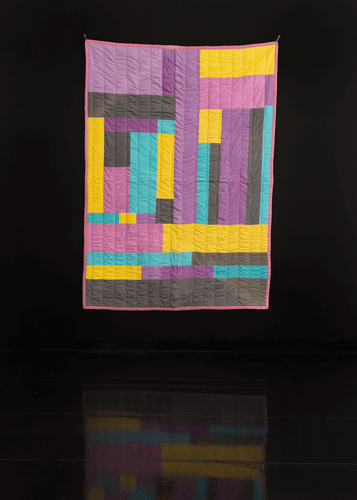 Handmade quilt with varying sizes of asymmetrical rectangles in bright yellow, purple, blue and grey.