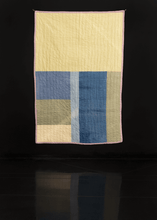 Handmade quilt with large rectangles in pastel yellow, green and blue.