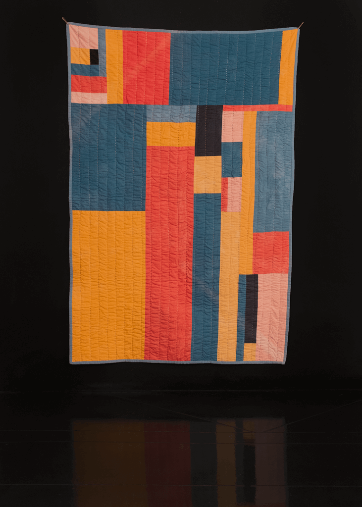 Handmade quilt with varying sizes of asymmetrical rectangles in bright yellow, pink, blue and red.