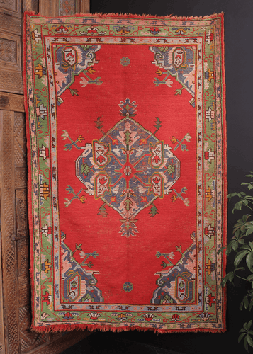 Turkish Oushak from the 1930s with a central medallion on a bright red ground. Framed by a green border and accents of pink, orange and blue.
