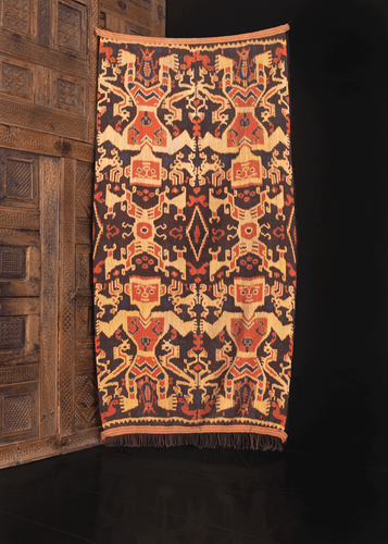 Vintage ikat handmade on the island of Sumba in Indonesia. Crafted in two strips featuring color palette of brown, gold and terra-cotta with indigo blue details.