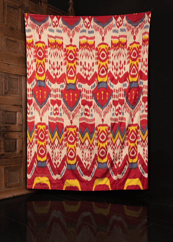 Silk ikat handmade in Uzbekistan. Silk front features a repeating abstract motif in yellow, red, blue and white atop a white field.