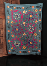 Suzani handmade in Uzbekistan during fourth quarter of 20th century. Six circular medallions in pink, purple, and blue atop slate ground.
