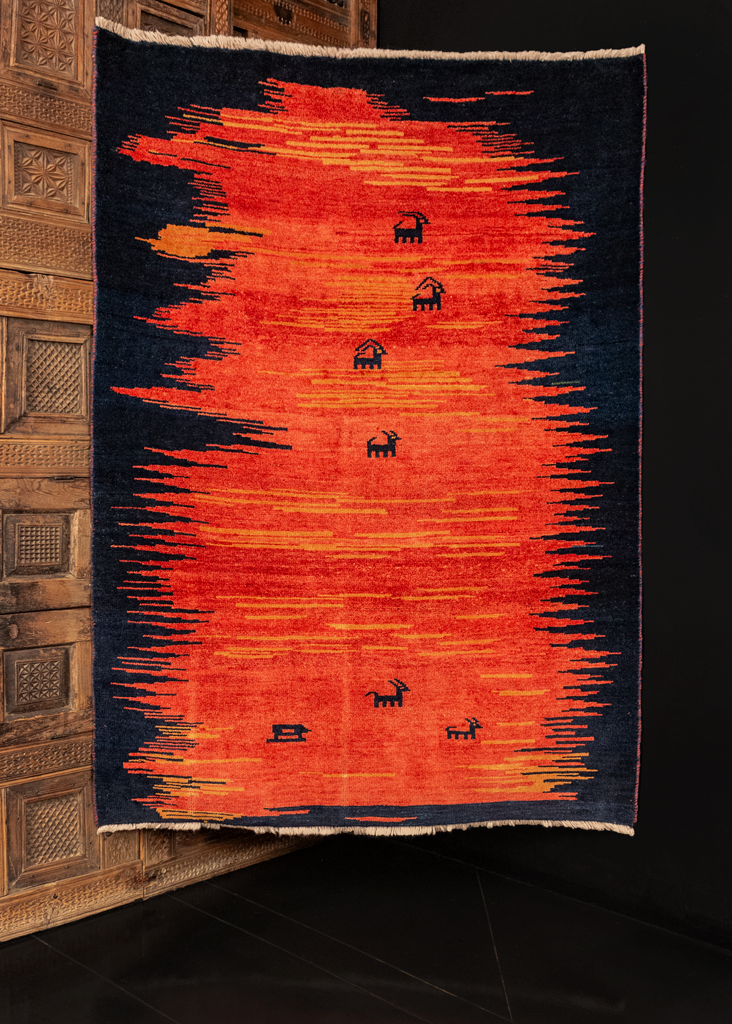 Handwoven Gabbeh rug made in Southern Iran during 21st century. Black field with a striking red and orange abstract pattern with small goats and animals woven throughout.