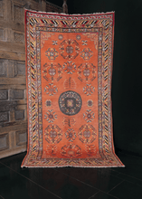 Khotan rug handwoven during second quarter of 20th century in Northwest China. Grey medallion with geometric floral drawings atop orange field. Showcases East Asian design elements like the lattice cornices and cloud band border.