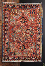 Persian Heriz rug handwoven during second quarter of 20th century. Geometric central medallion on a dark red field. Light and dark blues, golden camels and mint greens.