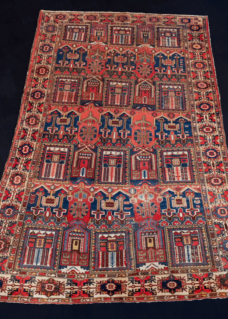 Bakhtiari Rug handwoven in Southern Iran during second quarter of 20th century. City-scape geometric design in red, blue, brown, yellow and ivory with a large main border.