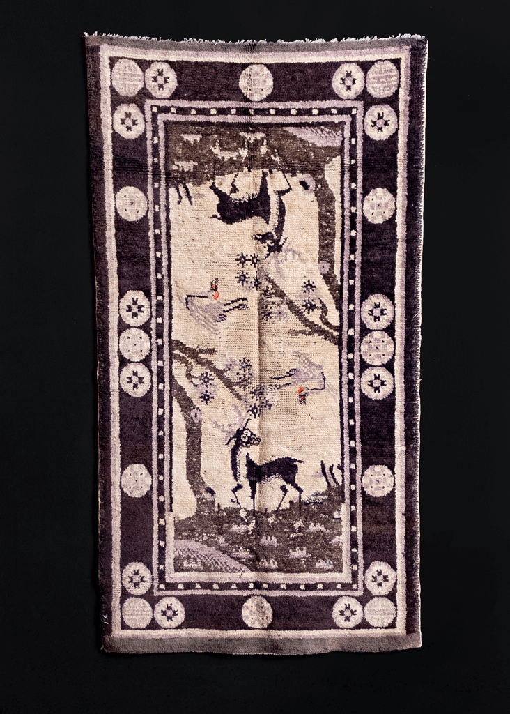 Pictoral Mongolian rug handwoven early 20th century. Mirrored design of a stag under a tree with a crane flying above. Black, gradations of grey and faded purple.