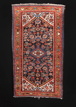Hamadan rug handwoven during second quarter of 20th century in Western Iran. Classic geometric design in red and blue with pops of yellow and ivory details. Herati pattered field surrounded by colorful border of alternating hearts.