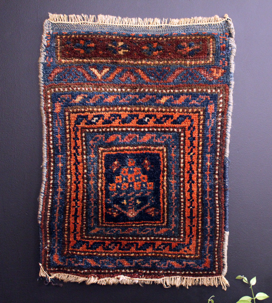 Small Kurdish rug with concentric borders that frame a bouquet of stylized flowers. Blues, oranges and reds.