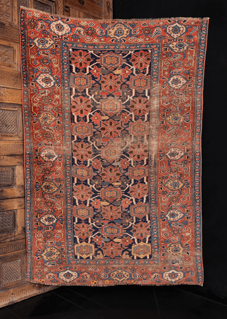 Bidjar rug handwoven during fourth quarter of 19th century. Wide border, deep blue field, and rosette pattern. Rusty oranges, reds and blues.