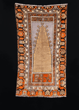 Prayer rug handwoven during second quarter of 20th century in Central Anatolia. Latch hooked mihrab woven with soft golden wool on a faded purple silver field.