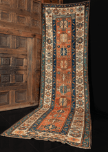 Runner handwoven in the Caucasus during late 19th century. Deep rust orange field with eleven small medallions in alternating shades of blue, yellow, brown, and green. Main border has an ivory field with a rosette pattern.