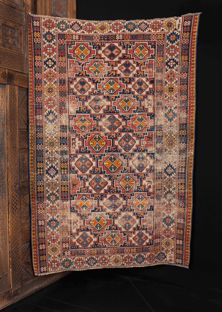 Shirvan rug handwoven in Caucasus turn of the 20th century. Geometric design of small medallions in diagonal columns surrounded by ivory border. Reds, greens, orange and blues contrasted with cream and brown wool.