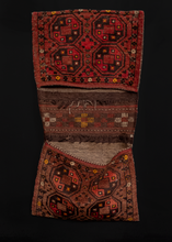 "Turkmen double saddlebag or ""Khorjin"" handwoven in Central Asia during middle of 20th century. Rosette design in sumac between the bag faces. Four large guns in the center framed by a thin border. Reds, browns and yellows."