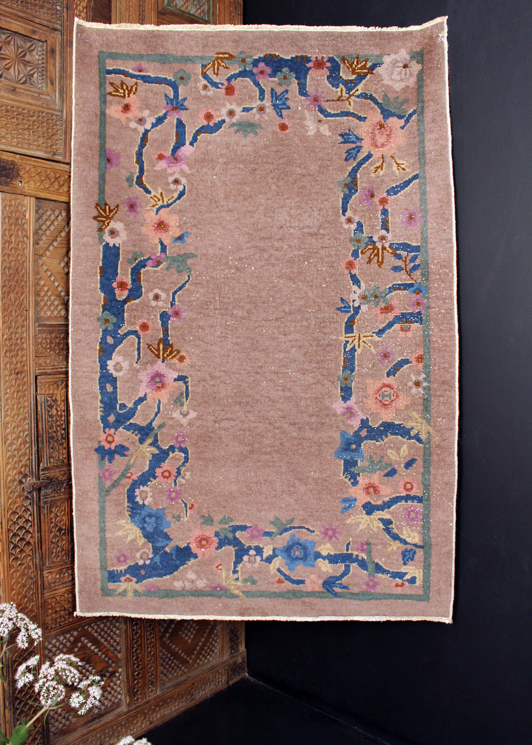 1930s Chinese deco rug featuring a mauve field with a border of colorful flowers growing on winding indigo branches.