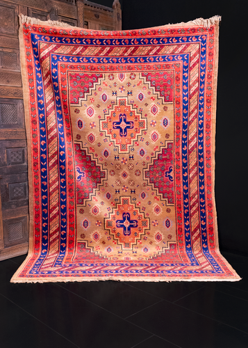 Khotan rug handwoven in Xinjiang region of Northwest China. Bold geometric patten with two medallions floating on a camel ground. Raspberry cornices filled with blue and orange flowers.