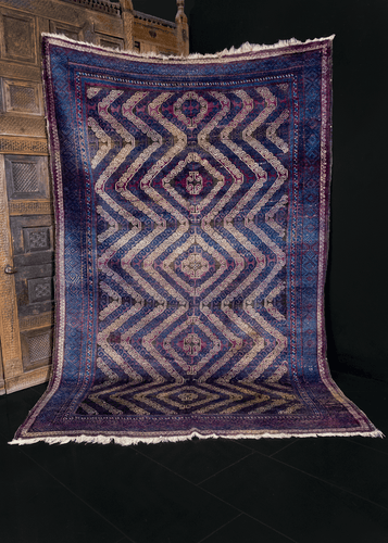 Mashwani Baluch rug handwoven in Afghanistan during second quarter of 20th century. Blue, ivory and purple field decorated with five curvilinear latch hook diamond medallions.
