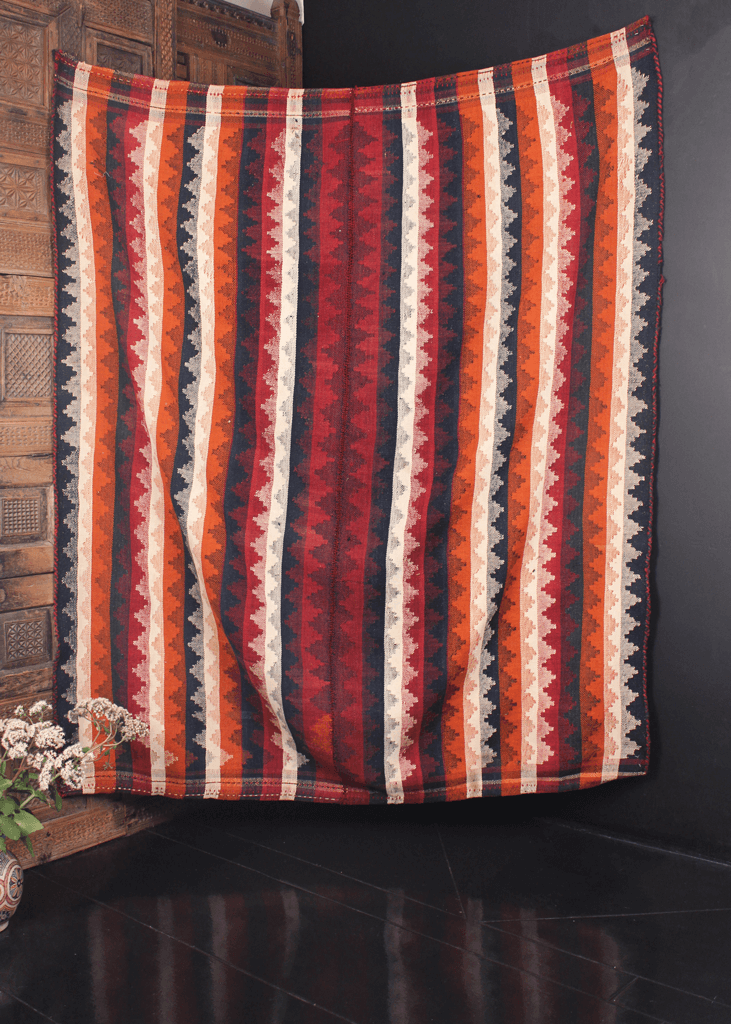 Early mid century multipurpose kilim woven in two pieces seamed at the center. Vibrating stripes with alternating triangles in white, orange, red and blue.