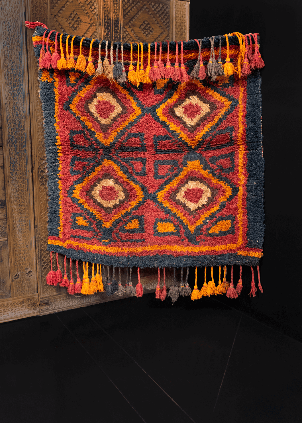 Vintage Julkhyr handwoven during third quarter of 20th century in Uzbekistan. Four diamond devices with surrounding polygons. Red and orange with black outlining and framing.