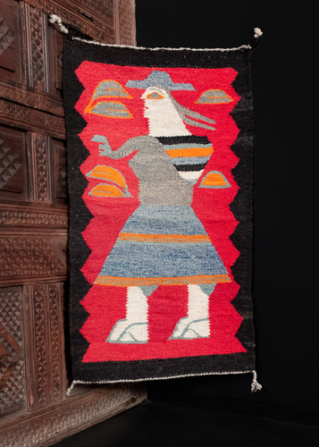 Navajo pictorial rug with a red field and black border. A woman is woven wearing a hat with a sack on her back.