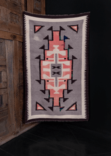 Navajo rug handwoven in Southwest US during second quarter of 20th century. Simple geometric design in pink, white and brown on heather grey field. Colorful repairs in green, blue and red.