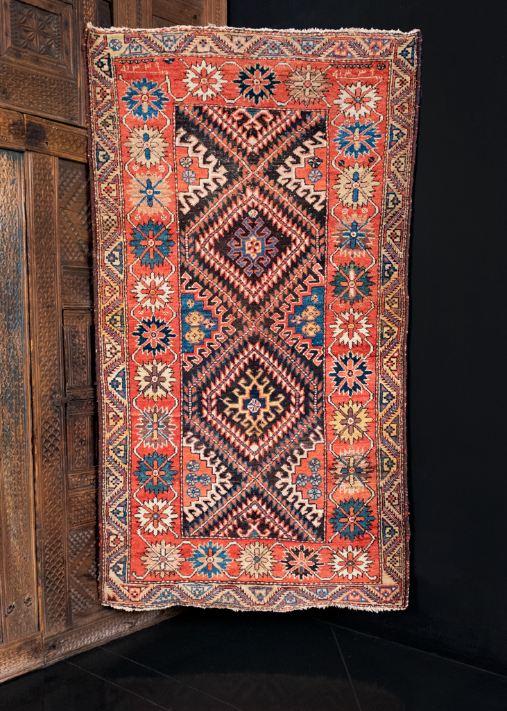 Kurdish rug handwoven during the first quarter of the 20th century in Northwest Iran. Bold geometric design of serrated diamonds and hooked polygons on a brown field.