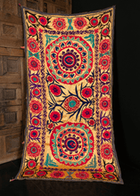 Suzani from Uzbekistan handmade during the third quarter of the 20th century. Two central medallions atop a pastel yellow ground. Flowers in bright pink and purple with green and black detailing.