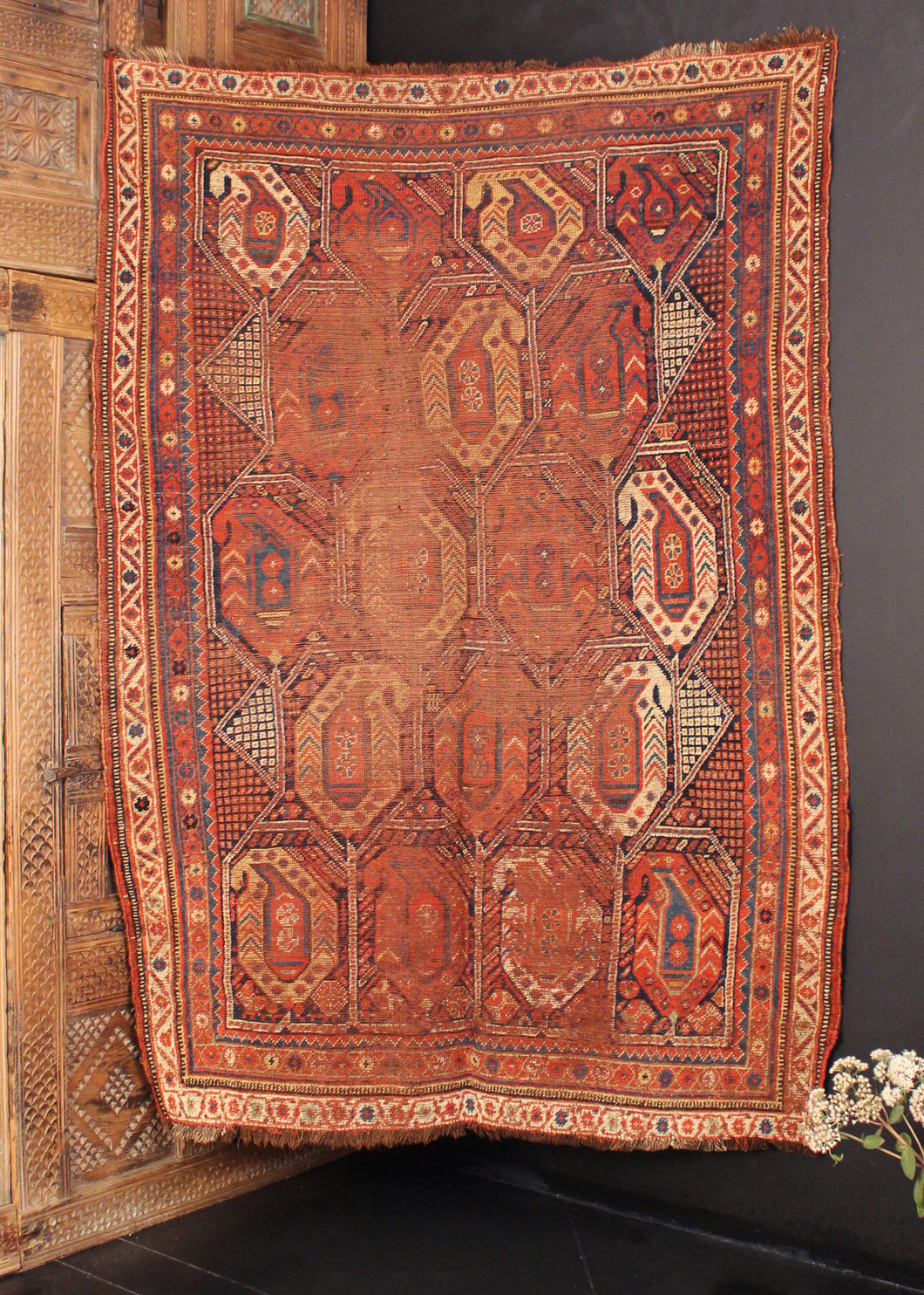 Qashqai rug handwoven at turn of the 20th century in Southwest Iran. Red, blue and yellow with white. Five rows of encapsulated botehs in rows of three or four.