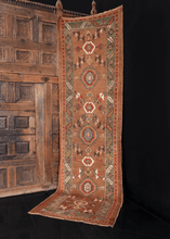 Kurdish runner handwoven in Northwest Iran during early 20th century. Large Kurdish rosettes flanked by serrated leaves in white, orange, blue, and green. Two small horses woven near the center.