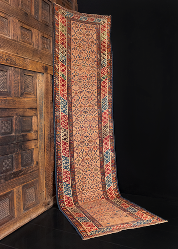 Shrivan runner handwoven in the Eastern Caucasus at the turn of the 20th century. Field is a variation on a lattice design woven in soft blues and yellows on a peach ground. Main border is a double S scroll design on a white ground.