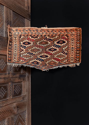Turkmen Asmalyk handwoven in Central Asia during middle of 20th century by Yomud tribesman. Traditionally used for Turkmen weddings. Soft aubergine and brighter peach tones with blues and reds.