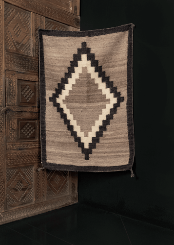 1920s Navajo rug with a central stepped diamond in white and black on a heather gray field. A thin black border frames the design.