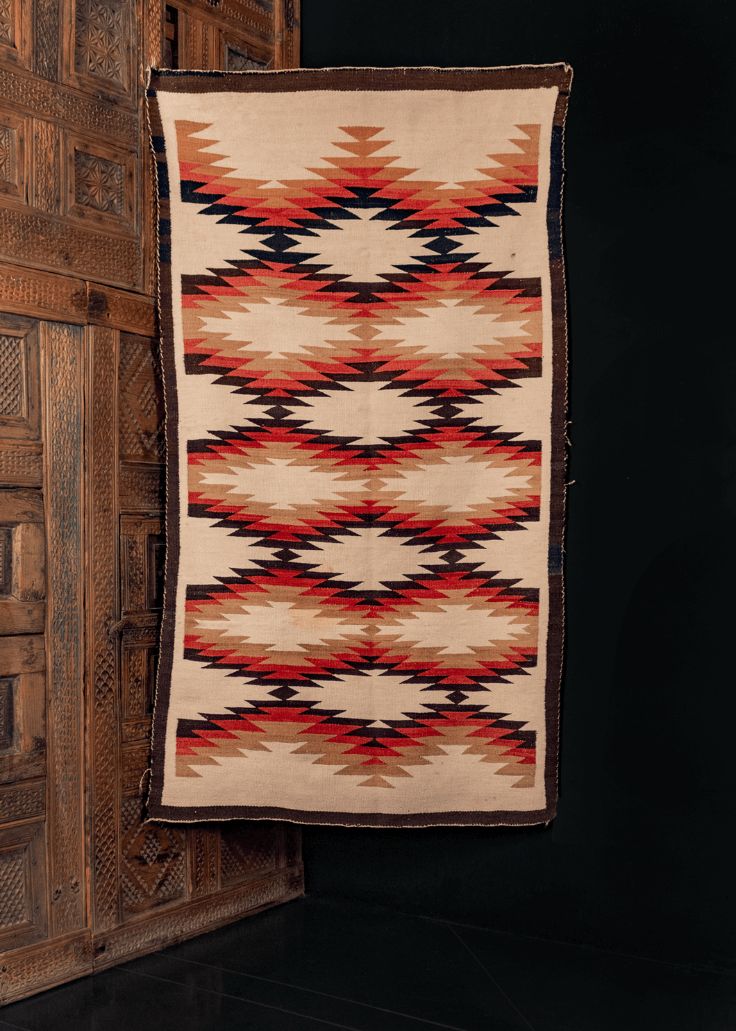 Navajo Flatwoven rug with a small-scale sunburst pattern in brown, pink, cream, ivory, earth tones.