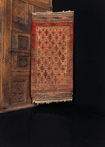 Antique Baluch rug with a hooked-diamond pattern on a camel ground, with 's' main border and kilim skirt ends. Main colors are reds, browns, and blues.