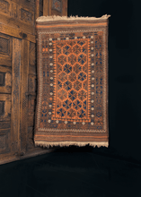 Vintage Baluch rug handwoven at the Afghan/Iran border during second quarter of 20th century. Woven in earth tones of pumpkin, chocolate, indigo and soft aubergine with pops of white. Main design of two-quartered leaves in a diagonal pattern.