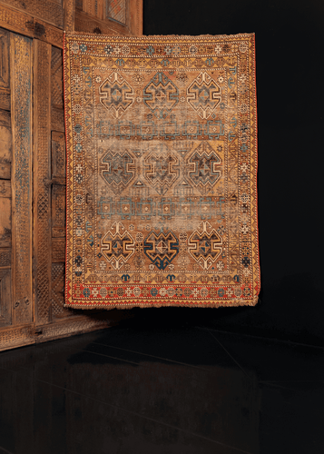 Shirvan rug handwoven in Caucasus during first quarter of 20th century. Geometric pattern of hooked squares and shield like lozenges on camel ground. Golden hues and shades of blue with red.