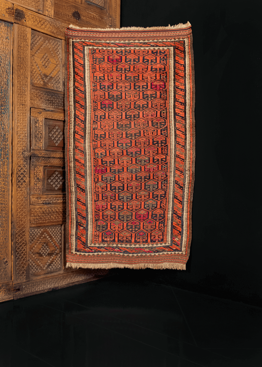 Baluch rug from the second quarter of 20th century with diagonal repeat design in reds, oranges, and browns with pops of fuchsia