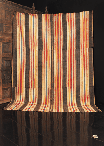 Rag Rug handwoven in the United States during the early 20th century. Flat woven in multiple strips of fabric that were sewn together in blocks. Thin vertical lines of white, red, yellow and blue contrast with broad black stripes.