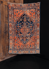 Hamadan rug handwoven in Western Iran during the second quarter of the 20th century. Rust orange central medallion on an inky blue ground.
