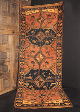 Mid century Persian Shiraz runner with warm color palette of orange, yellow and black. Five medallions containing camels, rosettes and various charms.