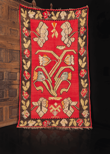 Bessarabian kilim from the second quarter of 20th century. Large scale geometric composition of flowers. Central flower motif on a bright red field framed by dark brown border with roses and leaves.