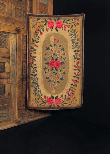 Hook rug made in New England during second quarter of 20th century. Wreath of flowers circling a central floral spray on a taupe ground. Earth tones of field contrast with bright pink of the roses and soft blues of flowers.