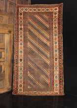 Caucasian Kazak rug dating from the late 19th century. Strong diagonal latch hook design in a color palette of ivory, brown, blue, red and yellow.